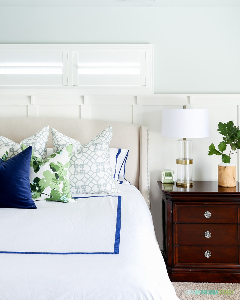 Master bedroom with white linens, Sherwin Williams Sea Salt Walls, navy blue velvet pillow, fig leaf pillows, trellis pillows, white board and batten and oak leaves.