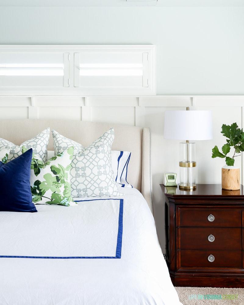 Master bedroom with white linens, Sherwin Williams Sea Salt Walls, navy blue velvet pillow, fig leaf pillows, trellis pillows, white board and batten and oak leaves.