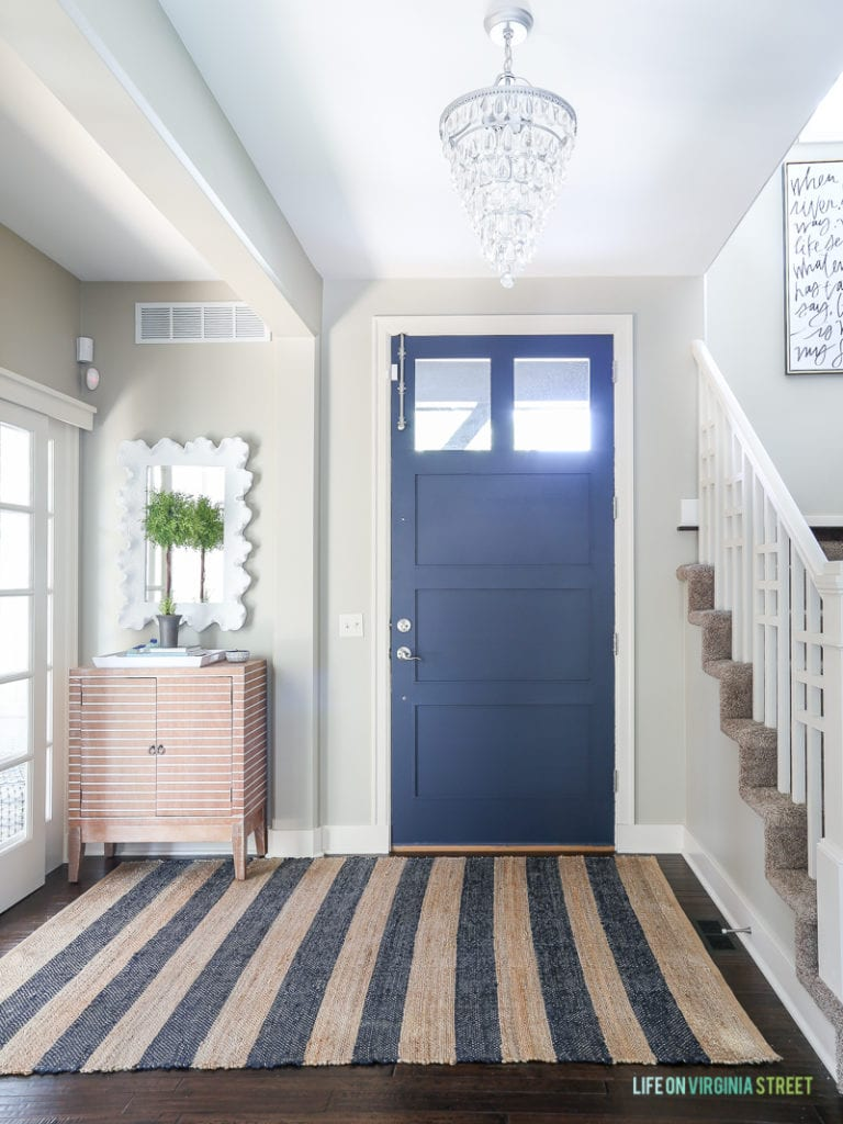 Entryway with navy blue front door, jute and navy striped rug, mossy topiary, white coral mirror, crystal chandelier and striped wood cabinet. Wall color is Behr Castle Path and door color is Benjamin Moore Hale Navy.