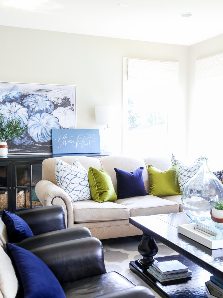 Fall living room with blue pumpkin artwork, neutral sofa, chartreuse and navy blue velvet pillows and olive leaf branches.