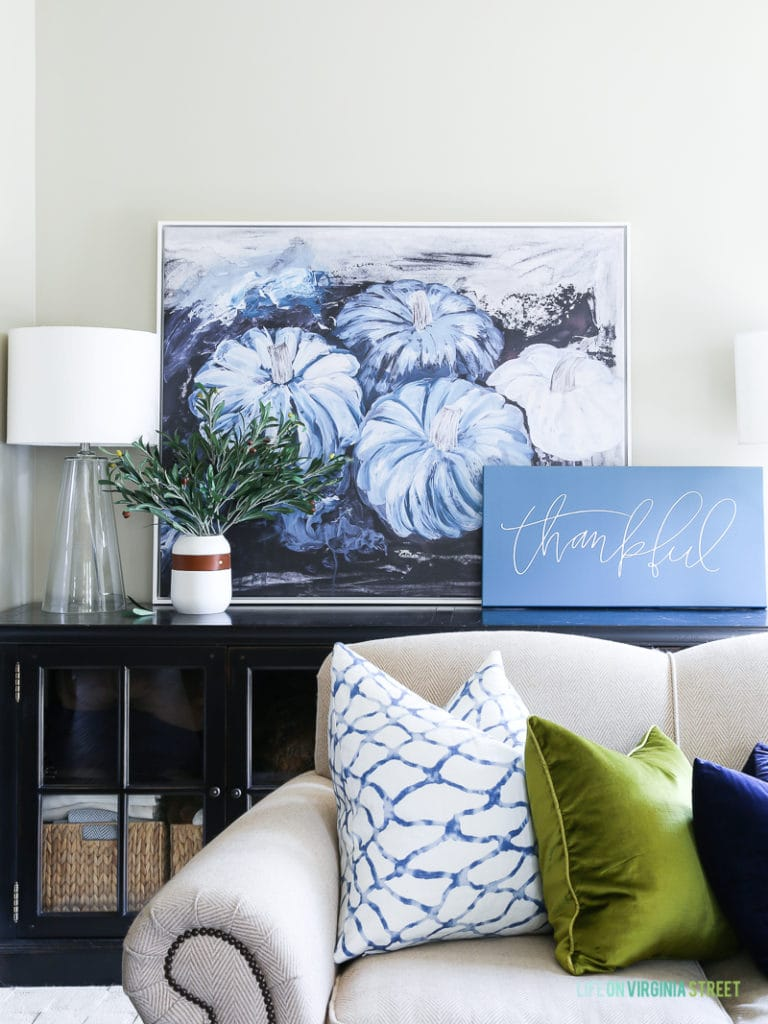 Fall living room with blue pumpkin artwork, neutral sofa, chartreuse and navy blue velvet pillows, glass lamps, and olive leaf branches.