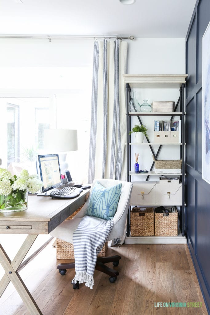Office with white oak hardwood floors, linen chair, blue and white striped drapes and navy blue board and batten wall.