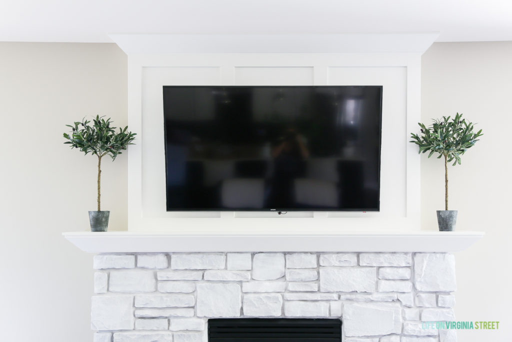 White stone fireplace with topiaries on the mantel and a TV hanging above it.