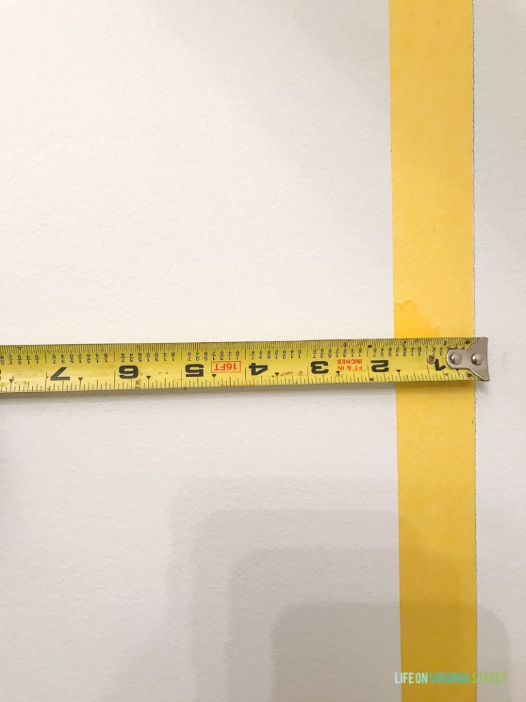 The yellow tape on wall and a measuring tape.