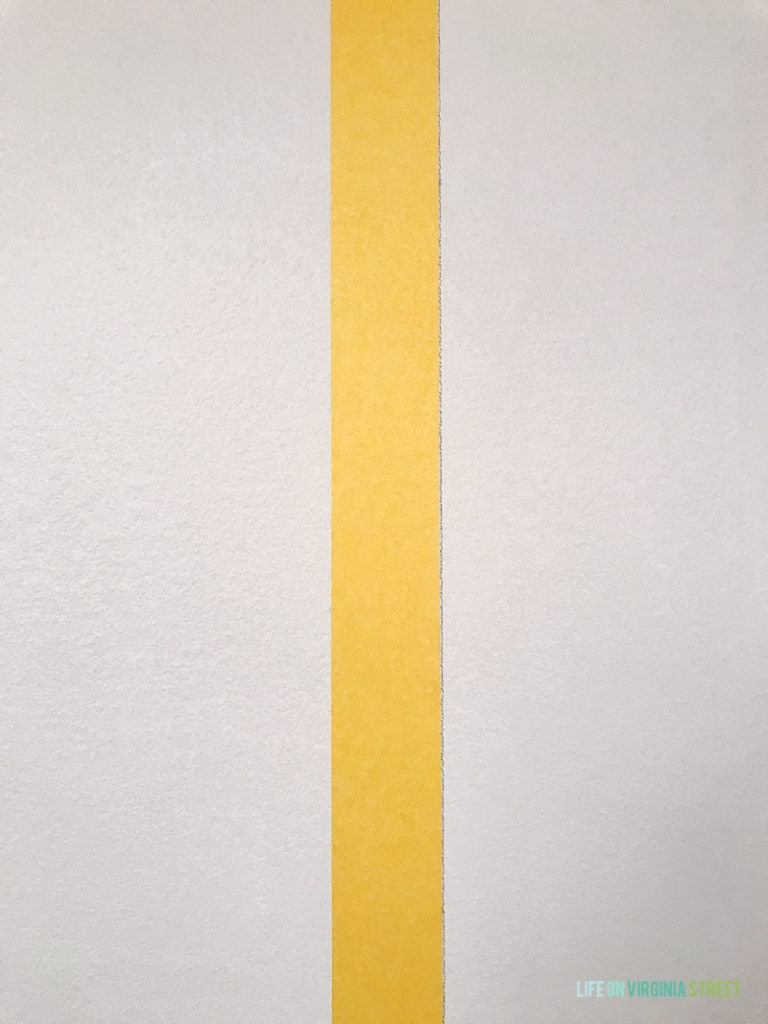 Pencil line beside the yellow tape on wall in laundry room.