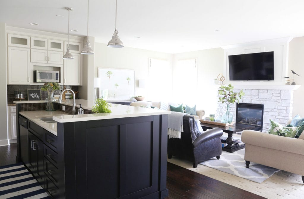 A kitchen island plus living room chairs and dark floors.