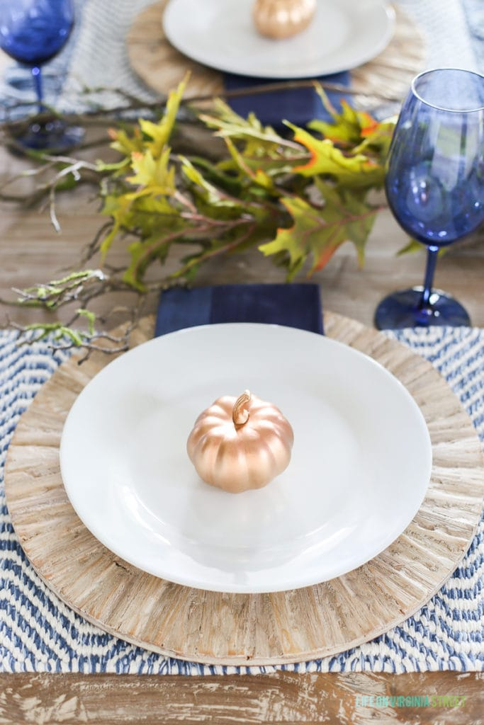 A blue Thanksgiving place setting with driftwood chargers and woven blue and white placemats and blue wine glasses.