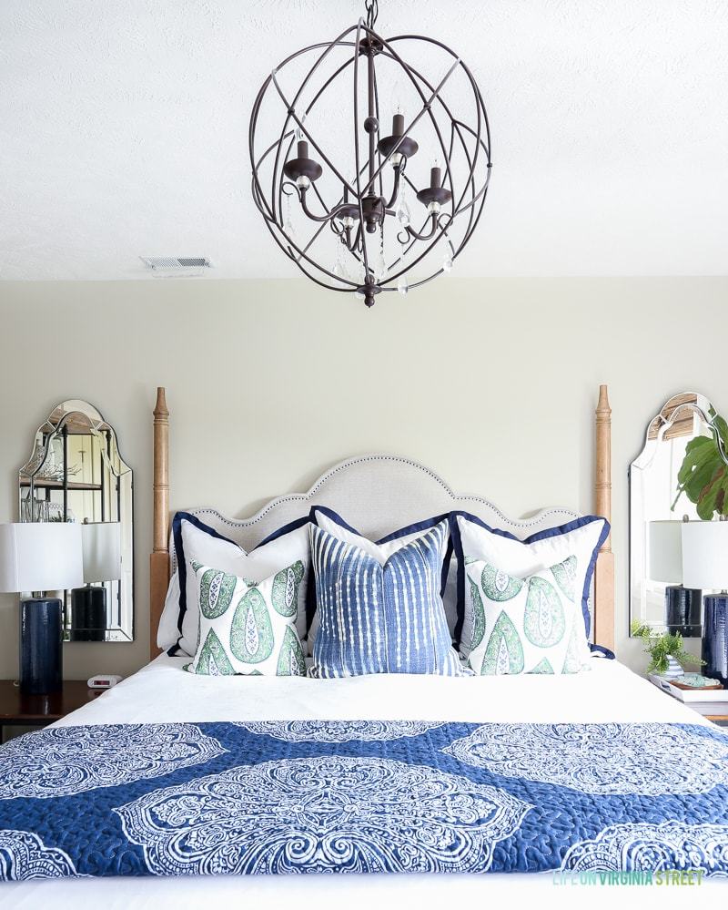 Mirror in corner, lamps on side tables, chandelier, and blue and white bedding in room.