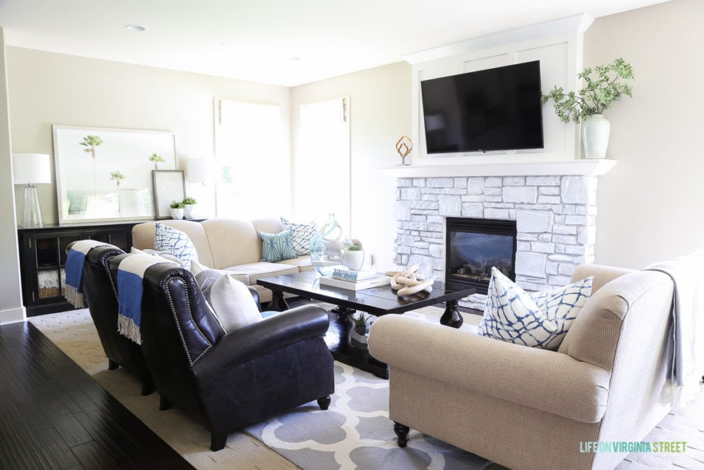 Living room chairs, a white brick fireplace, a tv above the fireplace, and a blue and white rug.