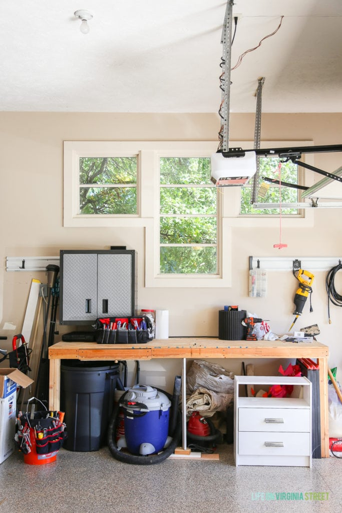 Wooden workbench in garage with tools on it.