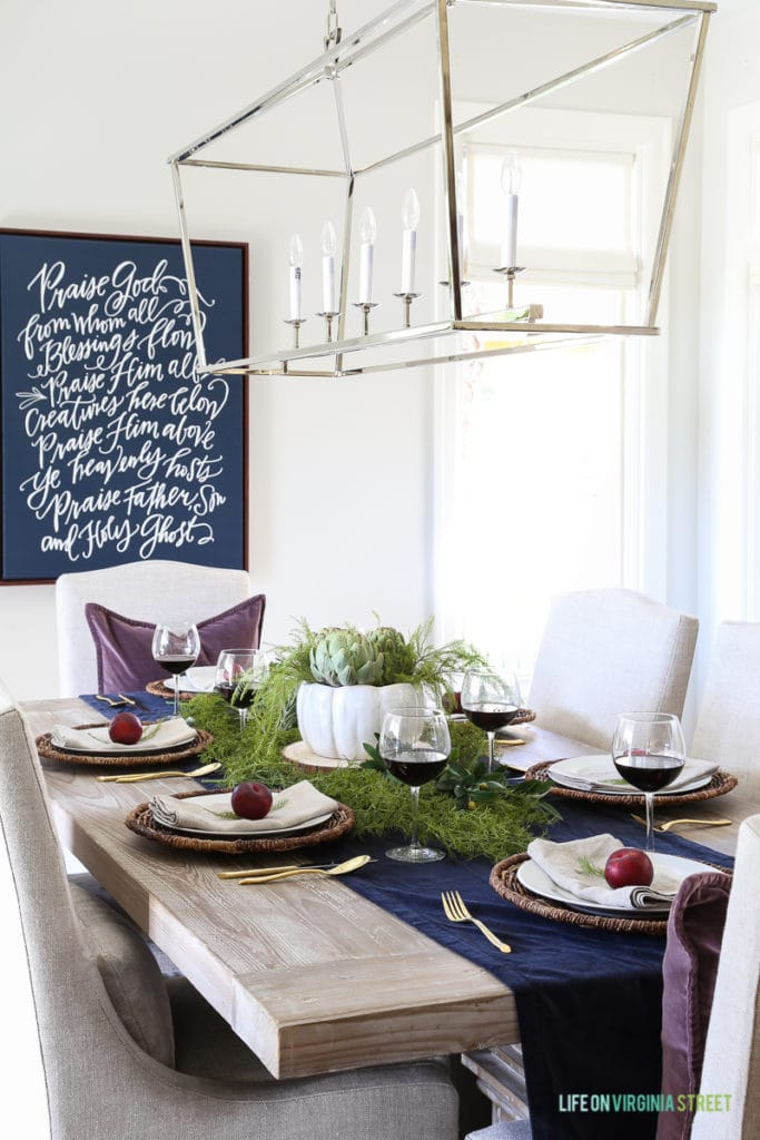 Olive, Plum and Artichoke Thankgiving tablescape. I'm loving that navy blue Doxology canvas with the fresh greenery and organic vibe of this place setting. Light fixture is the the Darlana Linear Pendant.