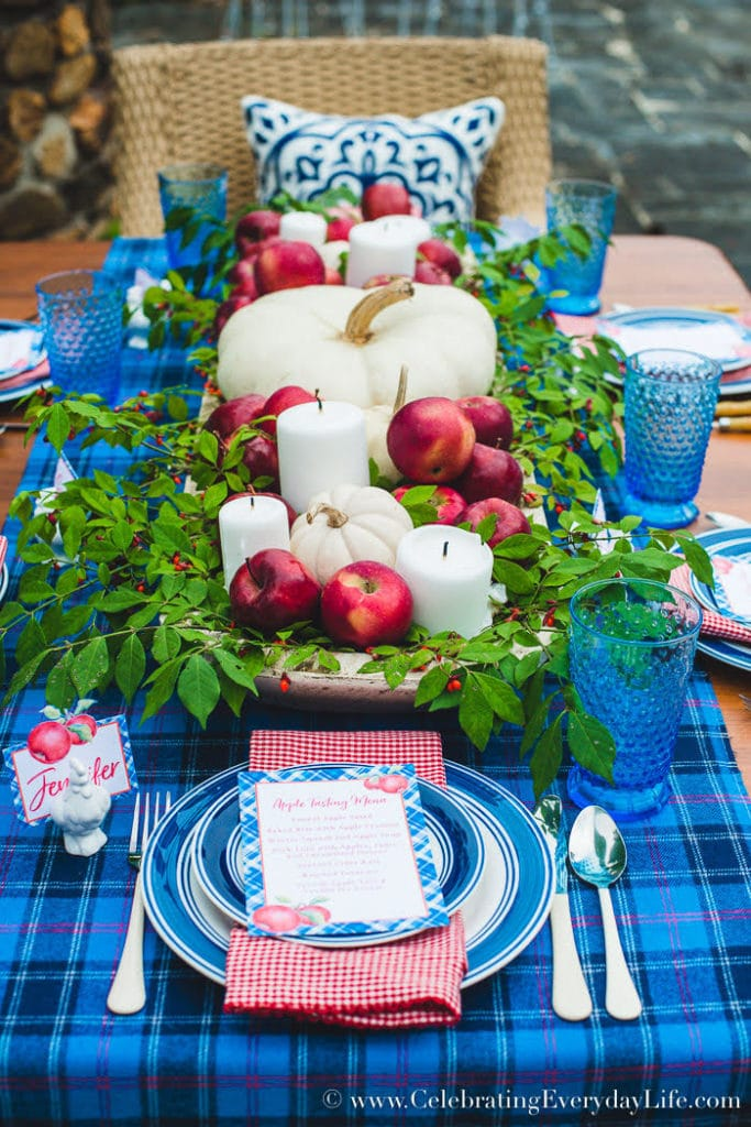 A blue plaid table runner with apples, candles and pumpkins as the centrepieces.