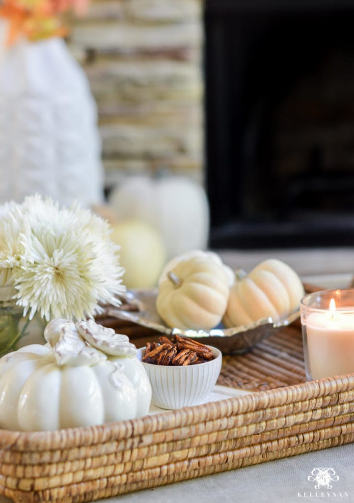 A wicker tray with white pumpkins, toasted pecans, and white flowers on it.