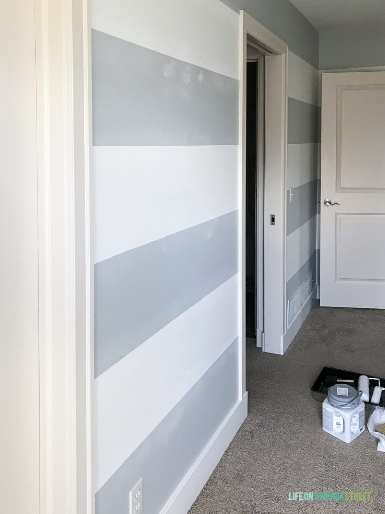 Blue and white striped wall in bedroom with paint can and roller on floor.