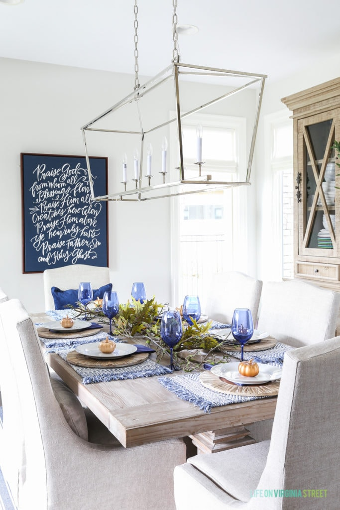Blue and white Thanksgiving dining room with navy blue doxology canvas, Darlana linear pendant, blue wine glasses, reclaimed wood table, and linen chairs.