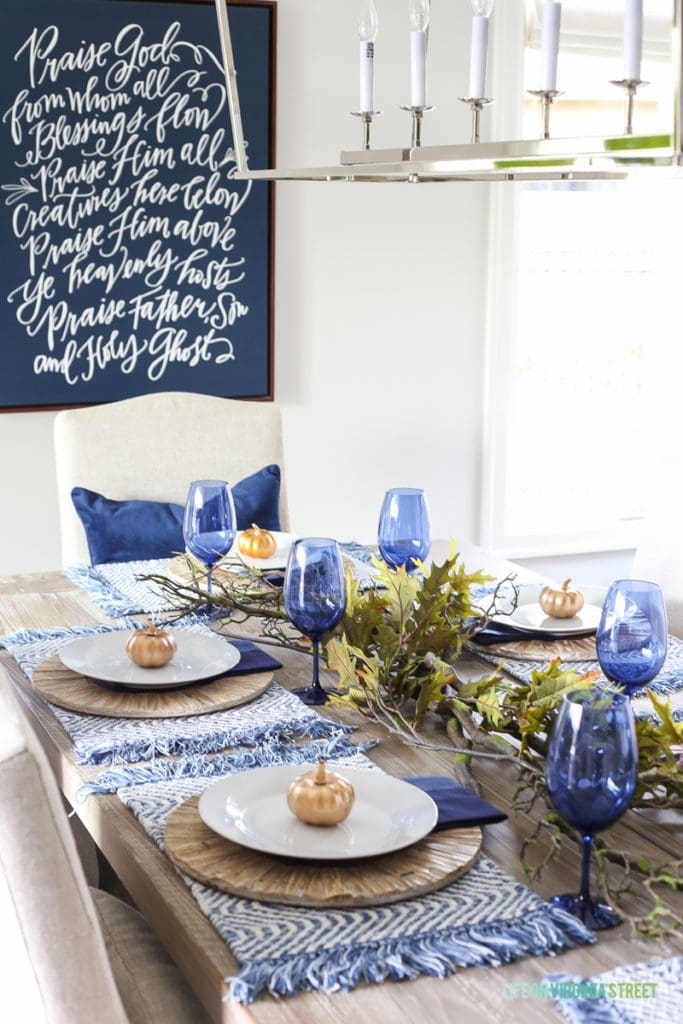 Blue and white Thanksgiving dining room with navy blue doxology canvas, Darlana linear pendant, blue wine glasses, navy blue velvet pillow, oak leaves and branches centerpiece, reclaimed wood table, and linen chairs.