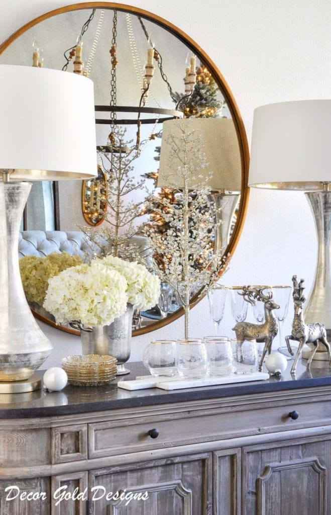 Gold mirror with white flowers and deer in living room.