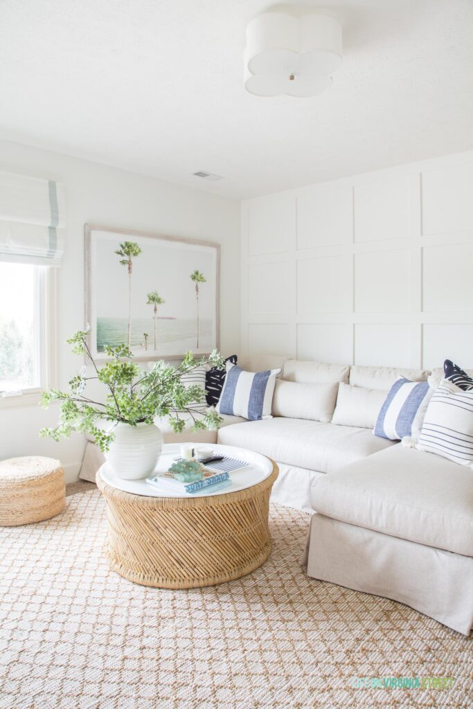 A living room with a round coastal coffee table, linen sectional, jute rug, palm tree art, board and batten grid wall, and blue and white decor.