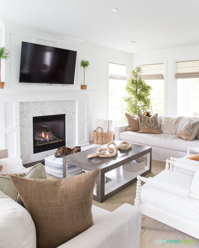 A modern coastal coffee table in a living room with white walls, marble fireplace surround, white spindle chairs, and brown linen pillows.
