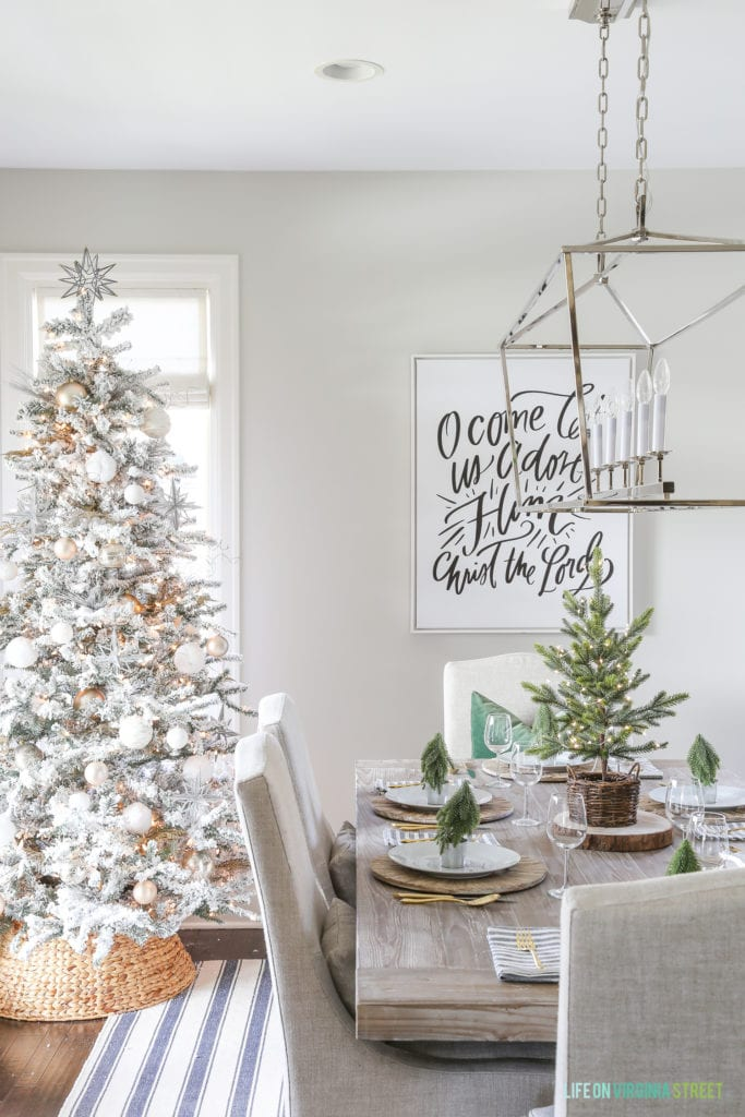 A neutral Christmas dining room with a navy blue striped rug, linen chairs, reclaimed wood dining table, large 'O Come Let Us Adore Him' canvas art, flocked Christmas tree, a seagrass tree collar, Darlana linear pendant light fixture and woodland coastal decor.