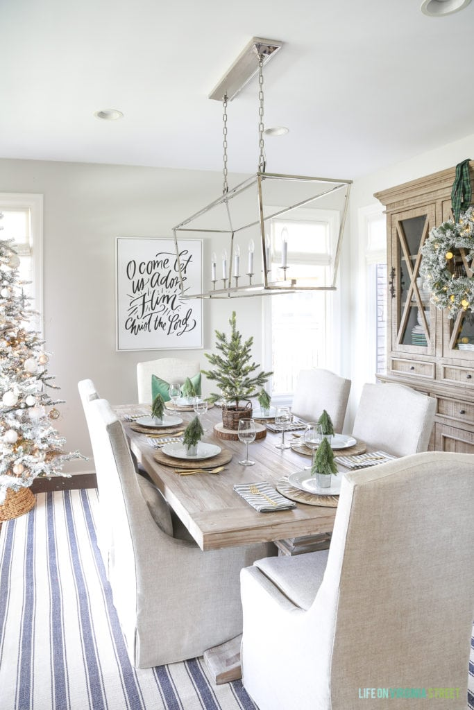 Design elements to compliment my woodland Christmas tablescape. A neutral Christmas dining room with a navy blue striped rug, linen chairs, reclaimed wood dining table, Darlana linear pendant light fixture and woodland coastal decor.