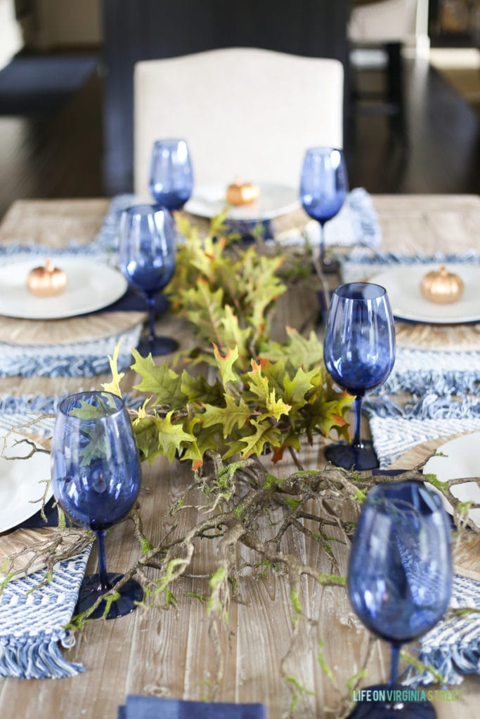 Touches of greenery add life to driftwood charges and bright blue glasses in this gorgeous Thanksgiving tablescape.
