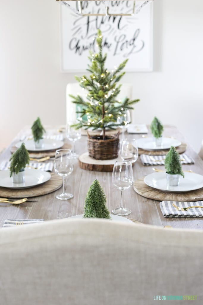A coastal woodland tablescape with a reclaimed wood table, linen chairs, green velvet pillow, and Christmas trees.