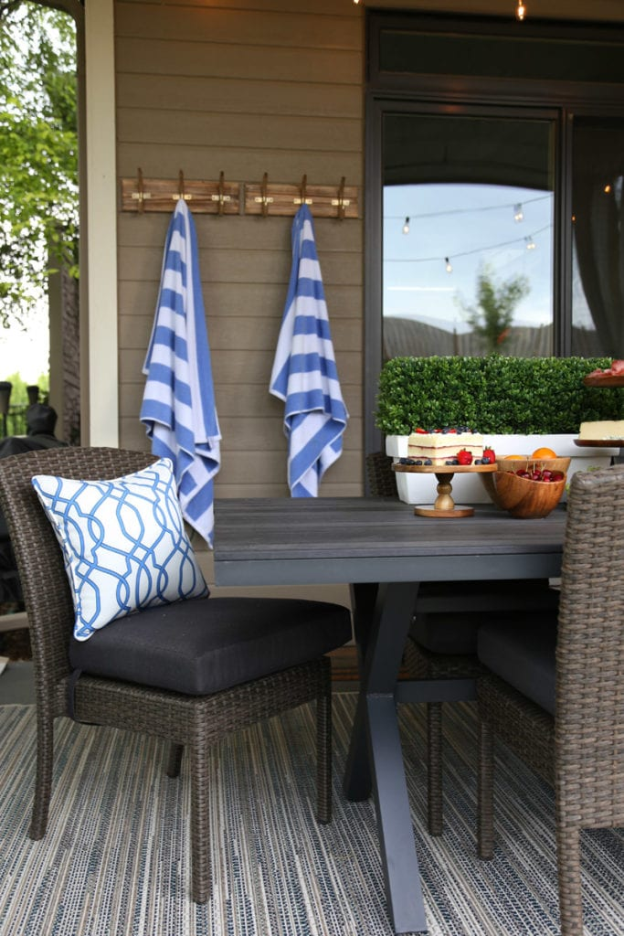 A wooden picnic table on the porch with outdoor chairs and blue and white cushions.