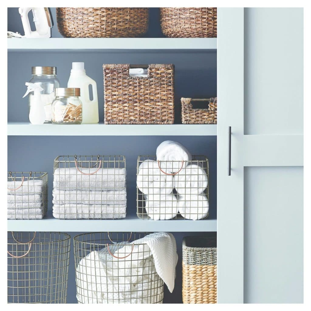 Organized linen closet using decorative baskets.
