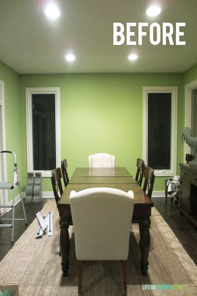 The dining room painted lime green with a small table in the centre of the room.