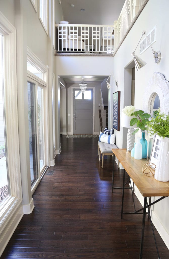 Entryway hallway with dark oak hardwood floors, swing arm sconce lights, gray front door, and unique railing balusters.