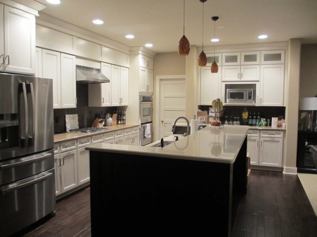 White cabinets, a white topped island and pendant lights in the kitchen.
