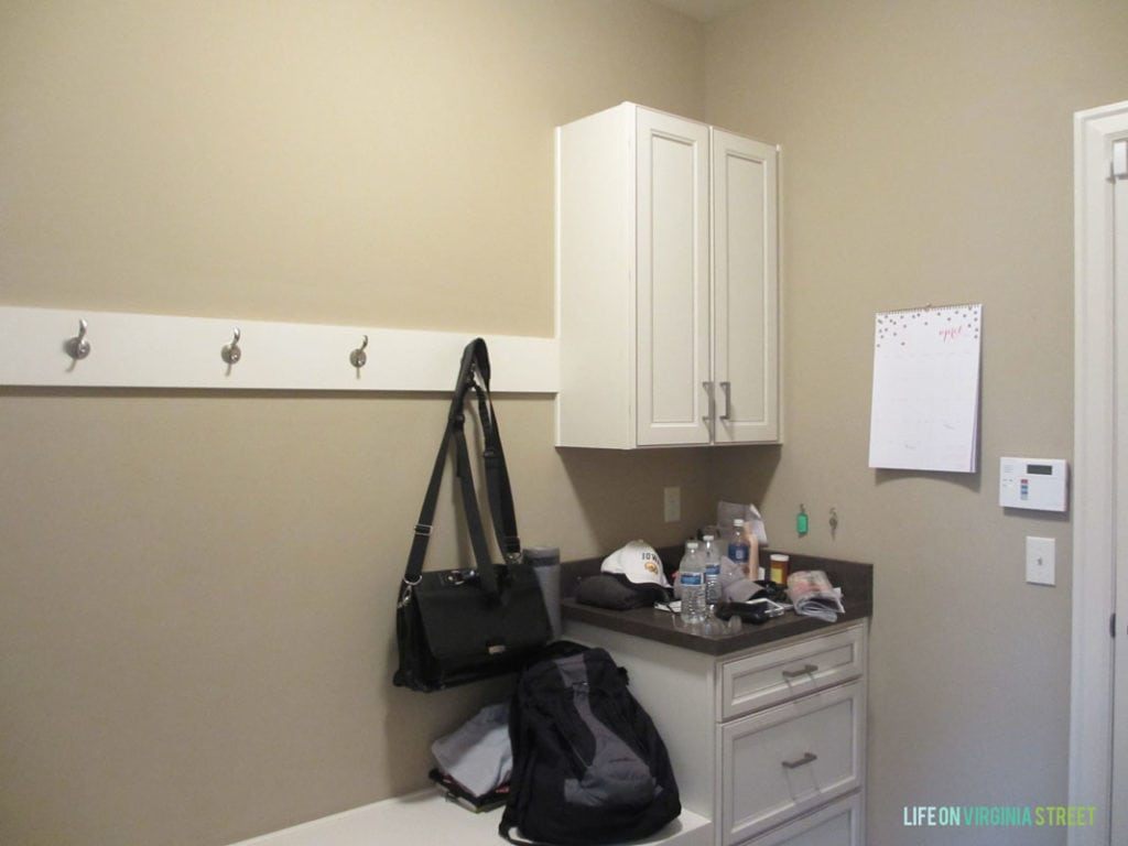 The mudroom with a small cabinet and drawers and hooks on the wall, plus a small white bench.