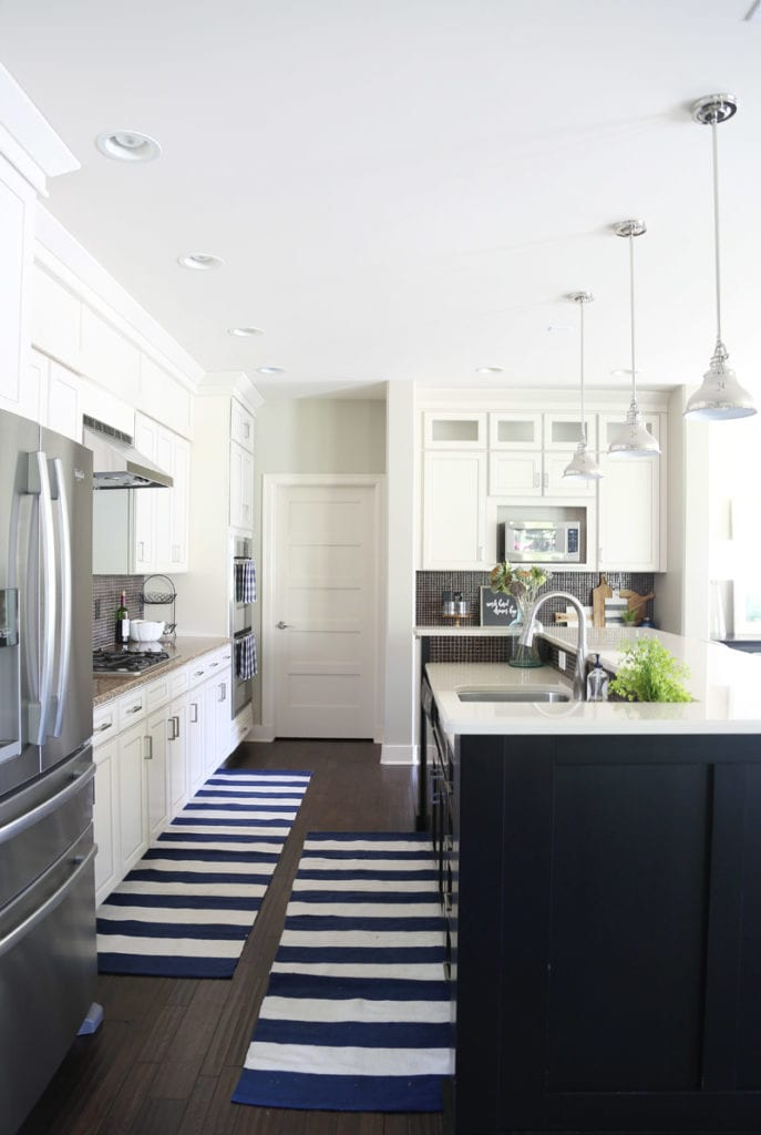 White kitchen with a black island and dark oak hardwood floors and striped blue and white runner rugs.