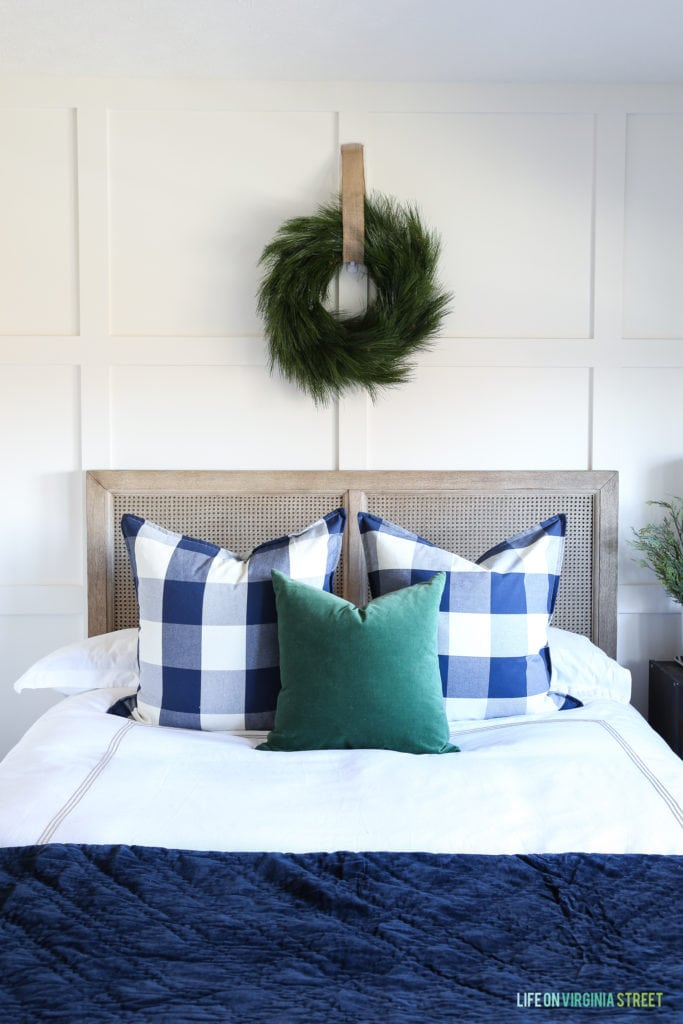 Coastal style bedroom with whitewashed cane wood bed, white bedding, wreath over bed, navy blue velvet coverlet, dark green velvet pillow and buffalo check pillows. Simple Christmas decorating ideas.