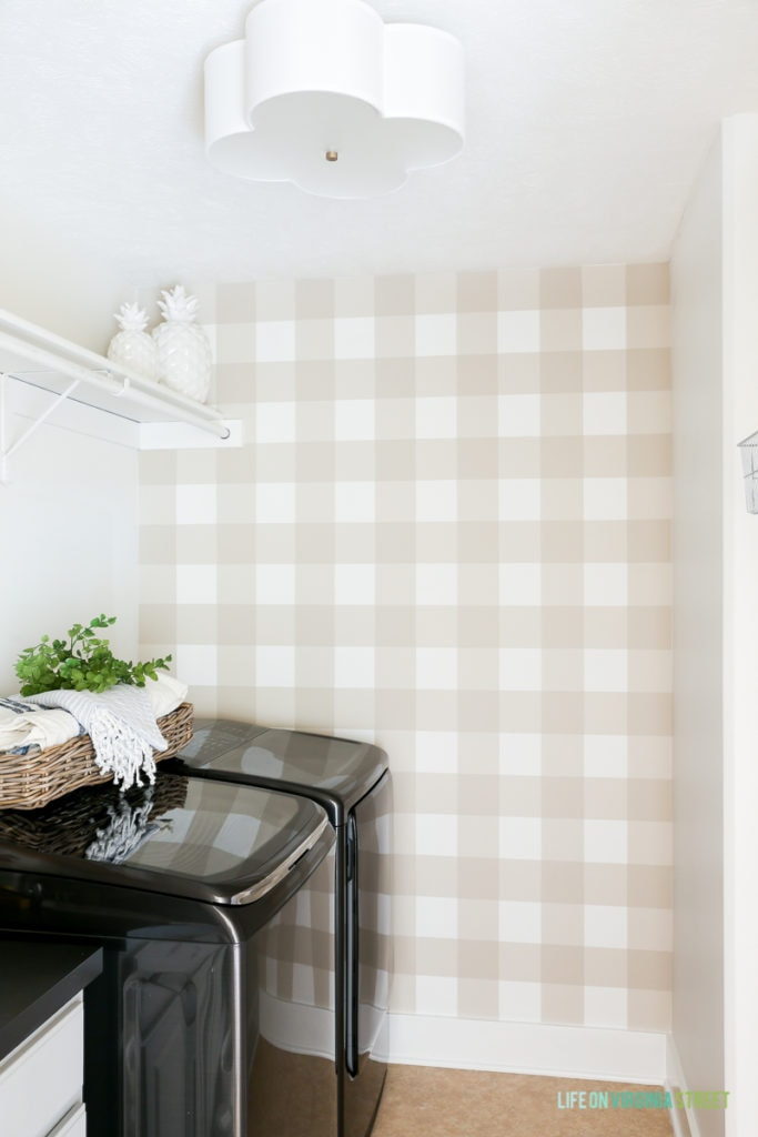 The laundry room with a black washer and dryer, plus a checkered wall. There are white pineapples on a shelf.
