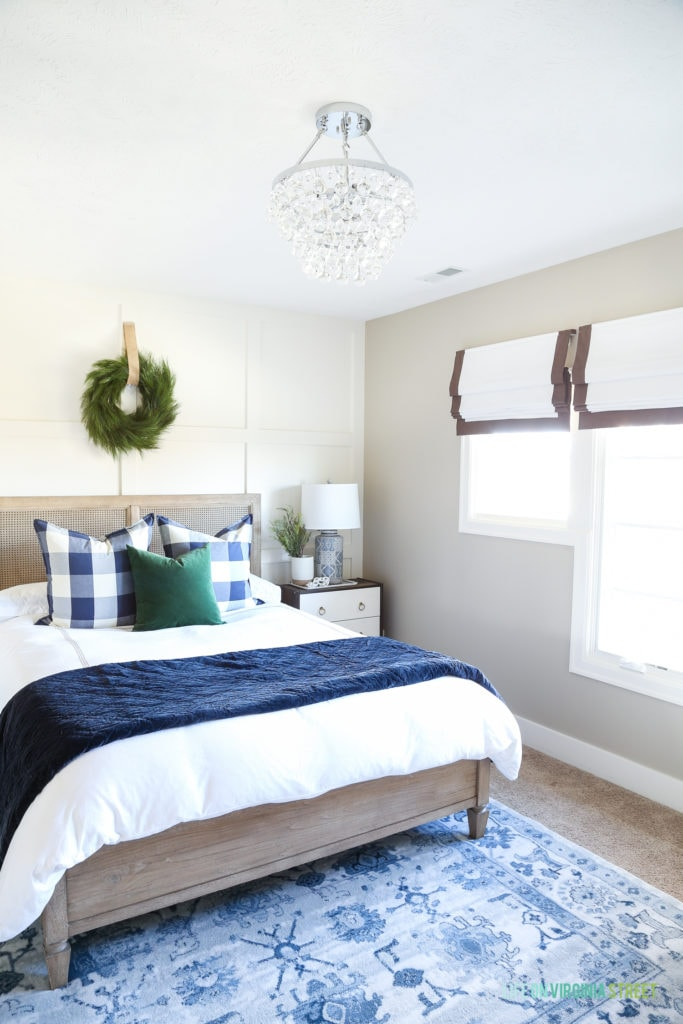 Blue and white bedroom with a crystal chandelier, driftwood color bed, white and navy blue bedding and buffalo check pillows.