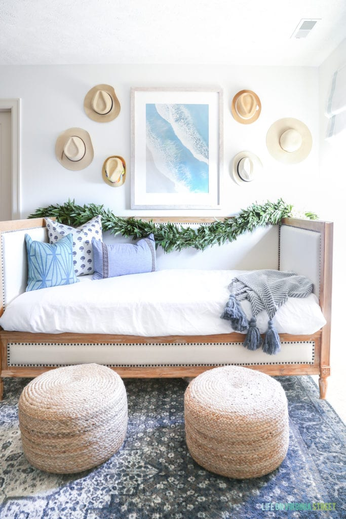 Wood and linen daybed, blue and brown vintage style rug, jute poufs, beach art, and hats on the wall.