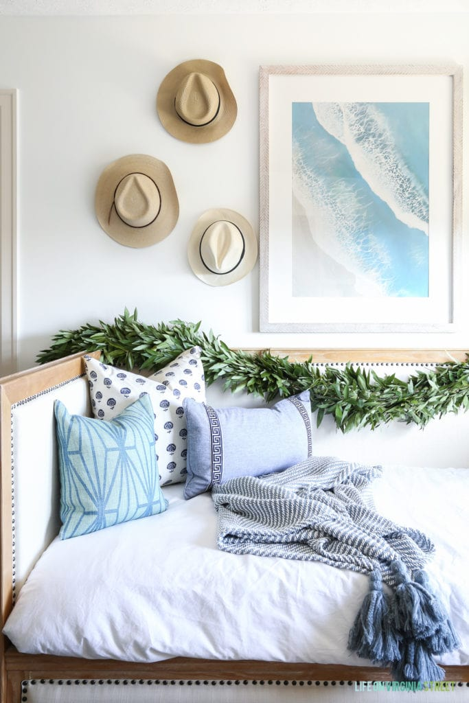 Christmas touches over a beachy daybed. I love the woven hats on the walls paired with the beachy artwork.