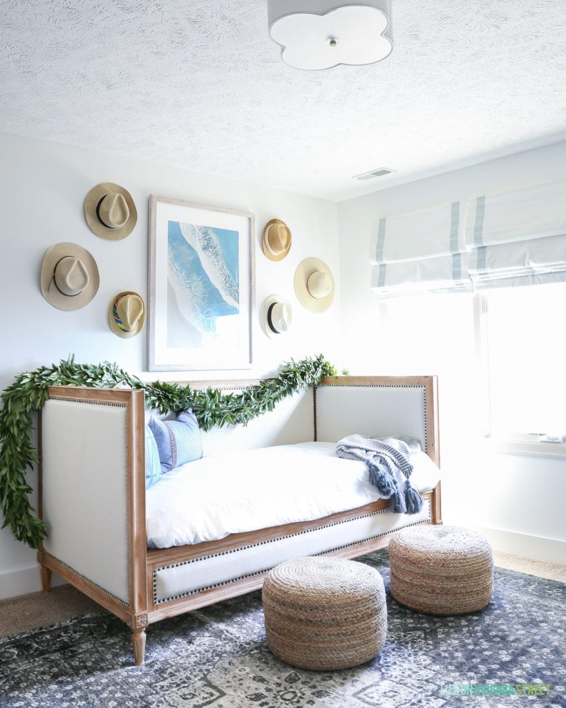 Daybed with white bedding, jute poufs, navy blue vintage rug, scalloped light fixture, beachy art and hats on the wall.