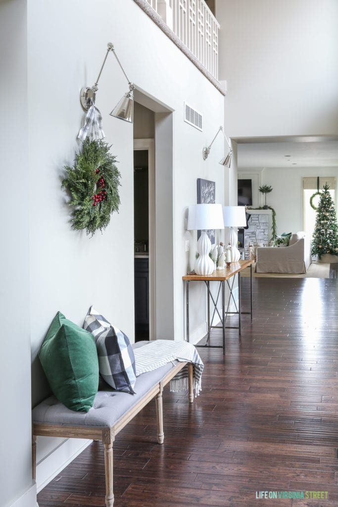 Christmas hallway with swing arm sconce lights, dark green velvet pillow, buffalo check pillow and simple Christmas decorations.