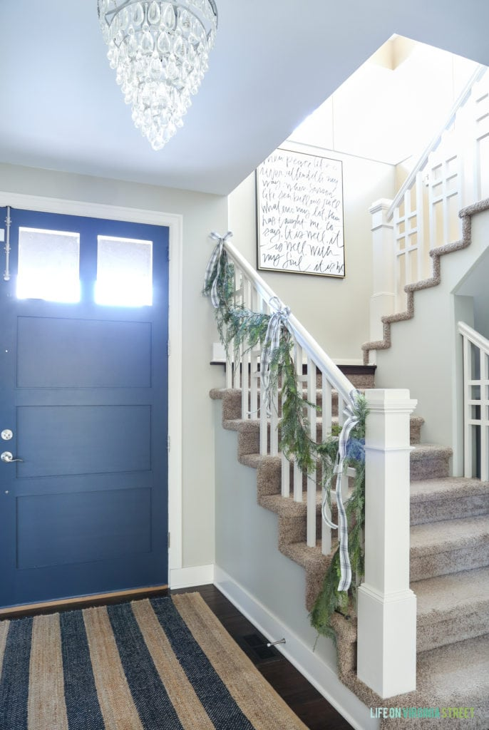 Christmas entryway with Benjamin Moore Hale Navy front door, unique staircase spindles, garlands, bows and a striped rug.