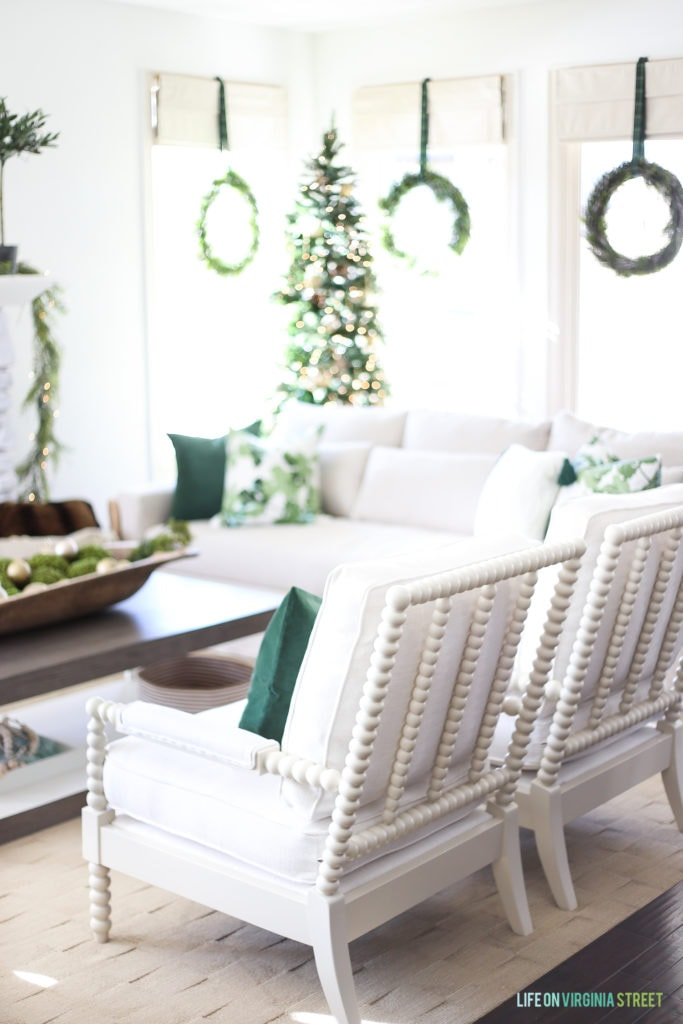 White spindle chairs with dark green velvet pillows.
