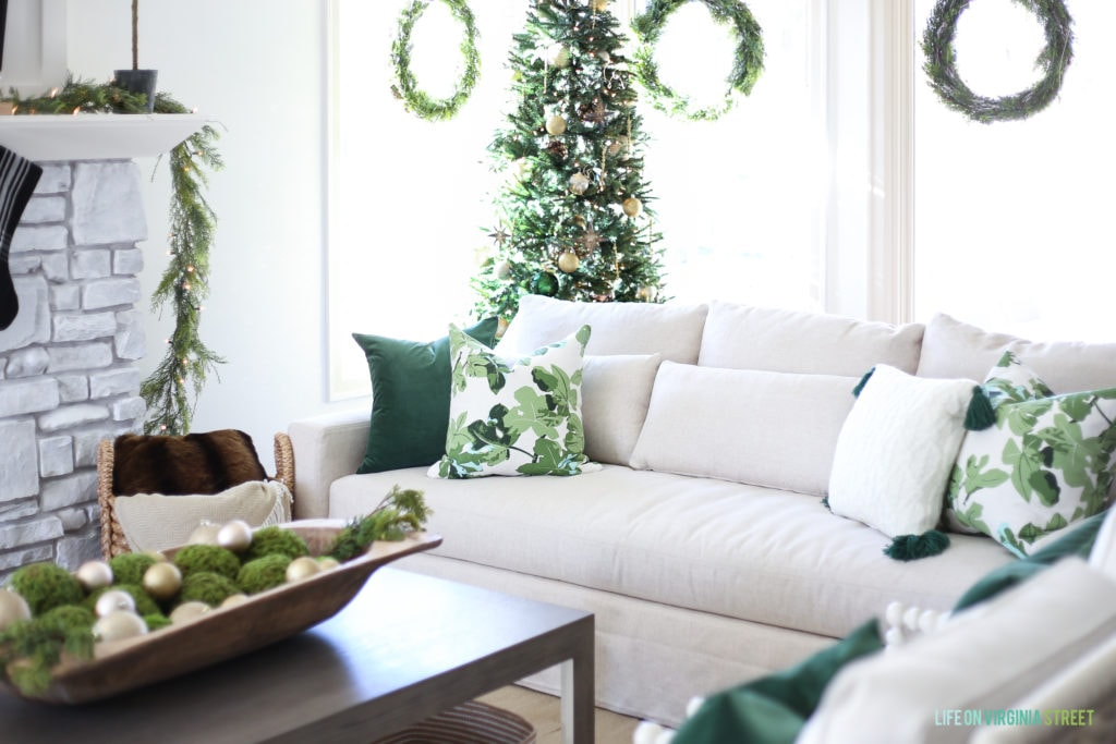 Linen slip-covered sofa with dark green velvet pillow and fig leaf pillows. Christmas tree with gold, brown and dark green ornaments.