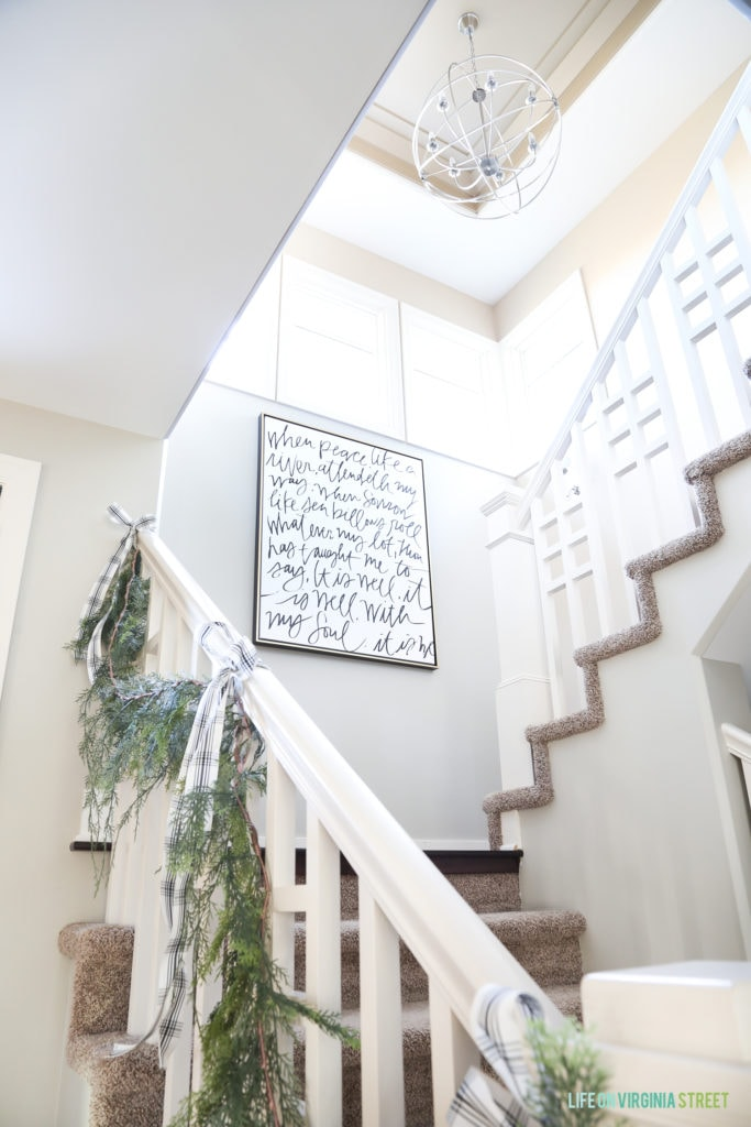 """It Is Well"" canvas hung in a Christmas staircase with garland and bows."