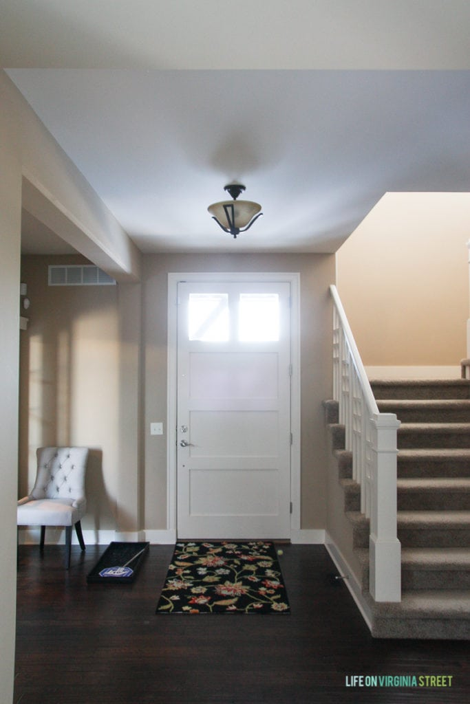The entryway of our home before picture with a small light and a floral rug.