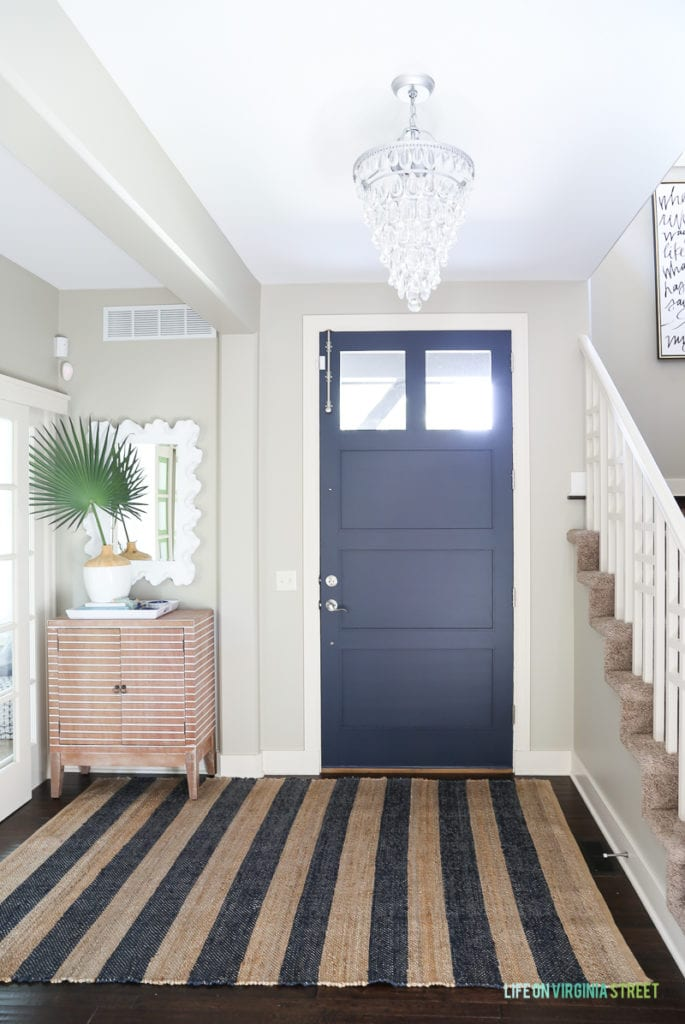 Coastal style entryway with a navy blue front door, greige walls, crystal chandelier, striped wood cabinet, and a navy and jute striped rug.