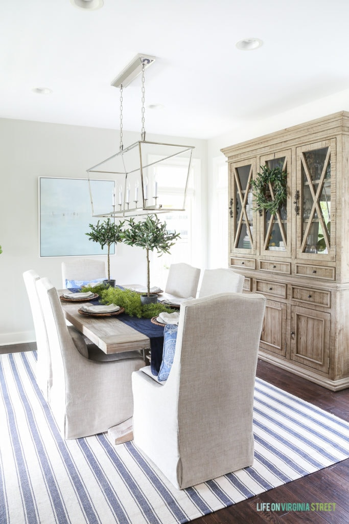 Traditional dining room with coastal accents. Reclaimed wood dining table, linen chairs, reclaimed wood hutch, Darlana linear pendant and beach art.