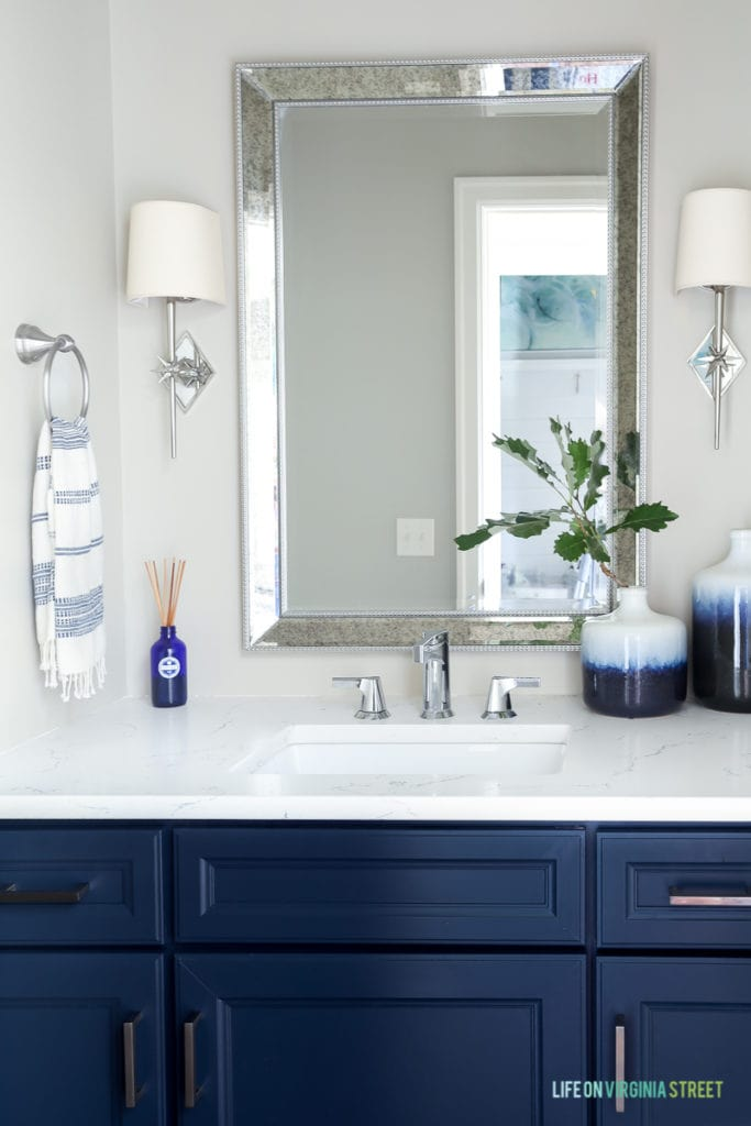 Powder bathroom with navy blue cabinets, tan walls, white quartz countertops, chrome star sconces and blue and white accents.