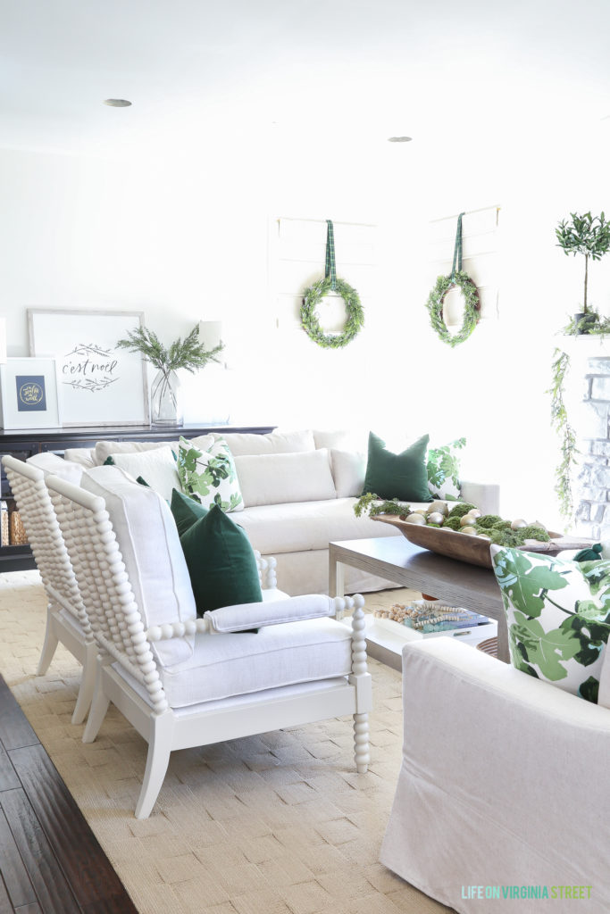 Christmas living room painted Benjamin Moore Simply white with white spindle chairs and linen York Slope Arm Sofas from Pottery Barn. I love the dark green velvet and fig leaf pillows and the wreaths on the windows! So perfect for the holidays!